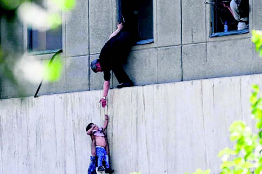 ஈரான் நாடாளுமன்றத்தில் தாக்குதல் நடைபெற்றபோது சிறுவனை பாதுகாப்பாக மீட்ட அதிகாரிகள். படம்: ராய்ட்டர்ஸ்